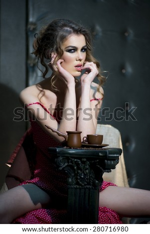 Portrait of glamour sexual girl with curly hair in red dress looking forward sitting near brown cup of coffee in hand on black leather background, vertical picture - stock photo