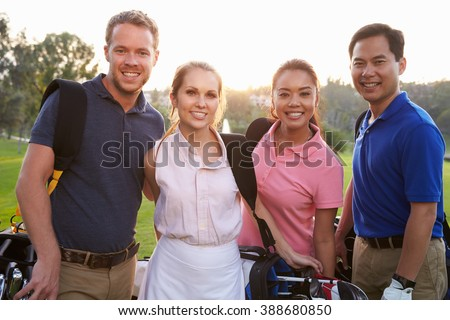 Portrait Of Golfers Walking Along Fairway Carrying Golf Bags - stock photo