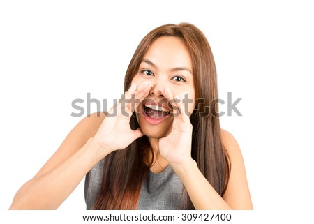 Portrait of good looking Asian girl, sleeveless top, light brown hair shouting announcement looking at camera, hands cupped around mouth amplifying sound. Thai national of Chinese origin. Horizontal
