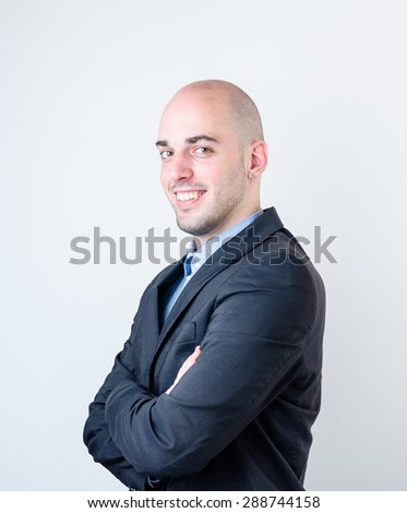 Portrait of good looking bald business man smiling on the white background