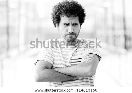 Portrait of good looking guy with angry face in urban background - stock photo