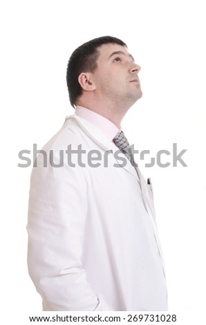 Portrait of good looking male doctor with stethoscope looks up. - stock photo
