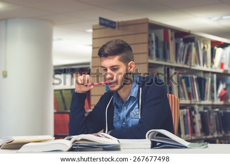 Portrait of good looking male student reading and doing research in the library. Lifestyle image of university student studying for exam with a vintage, blue filter applied. Knowledge is power concept - stock photo