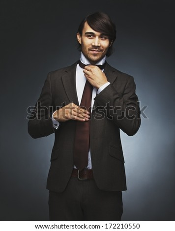 Portrait of good looking man in suit adjusting his necktie looking away at copyspace smiling. Young male fashion model in business attire against black background. Mixed race model. - stock photo