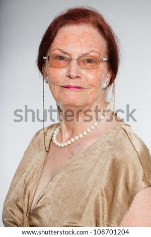 Portrait of good looking senior woman wearing glasses with expressive face showing emotions. Smiling. Acting young. Studio shot isolated on grey background. - stock photo