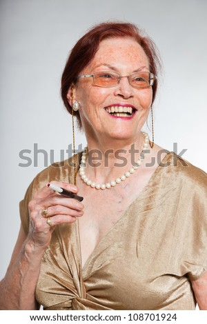 Portrait of good looking senior woman wearing glasses with expressive face showing emotions. Smoking a cigarette. Acting young. Studio shot isolated on grey background.
