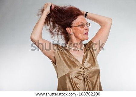 Portrait of good looking senior woman wearing glasses with expressive face showing emotions. Happy and free. Acting young. Studio shot isolated on grey background. - stock photo