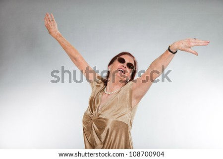Portrait of good looking senior woman wearing sunglasses with expressive face showing emotions. Happy and free. Acting young. Studio shot isolated on grey background.