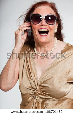 Portrait of good looking senior woman wearing sunglasses with expressive face showing emotions. Calling with cell phone. Acting young. Studio shot isolated on grey background.