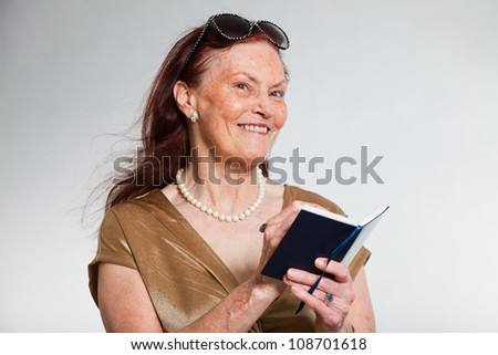 Portrait of good looking senior woman wearing sunglasses with expressive face showing emotions. Holding agenda. Acting young. Studio shot isolated on grey background. - stock photo