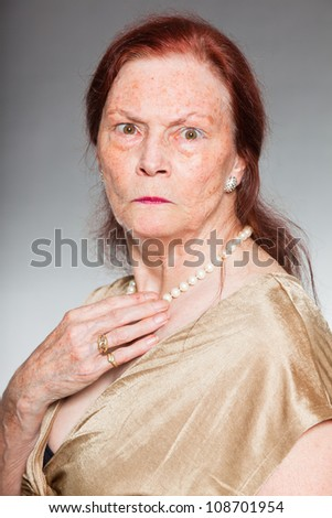 Portrait of good looking senior woman with expressive face showing emotions. Angry. Acting young. Studio shot isolated on grey background.