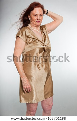 Portrait of good looking senior woman with expressive face showing emotions. Happy and free. Acting young. Studio shot isolated on grey background. - stock photo
