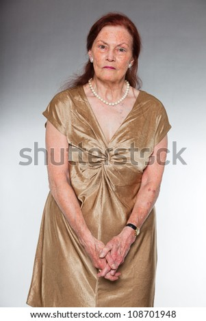 Portrait of good looking senior woman with expressive face showing emotions. Pensive and serious. Acting young. Studio shot isolated on grey background. - stock photo