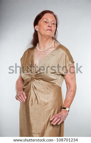 Portrait of good looking senior woman with expressive face showing emotions. Serious. Acting young. Studio shot isolated on grey background.