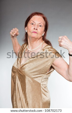 Portrait of good looking senior woman with expressive face showing emotions. Strong and healthy. Acting young. Studio shot isolated on grey background.