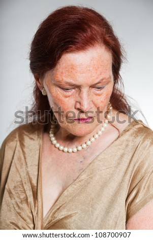 Portrait of good looking senior woman with expressive face showing emotions. Thinking and hoping. Acting young. Studio shot isolated on grey background.