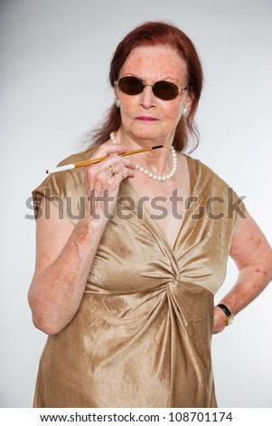 Portrait of good looking senior woman with expressive face showing emotions. Wearing sunglasses and smoking a cigarette. Acting young. Studio shot isolated on grey background. - stock photo