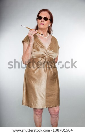 Portrait of good looking senior woman with expressive face showing emotions. Wearing sunglasses and smoking a cigarette. Acting young. Studio shot isolated on grey background.