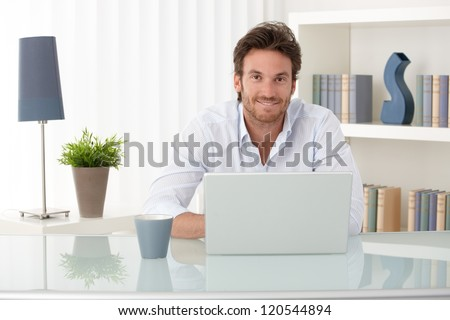 Portrait of goodlooking man sitting at table at home with laptop computer, smiling at camera. - stock photo