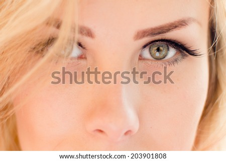 Portrait of gorgeous beautiful blond young lady face with gray or light green eyes looking at camera closeup picture - stock photo