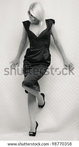Portrait of gorgeous blond woman in long black dress. Black and white - stock photo