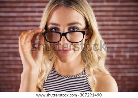 Portrait of gorgeous blonde hipster posing with glasses against red brick background - stock photo