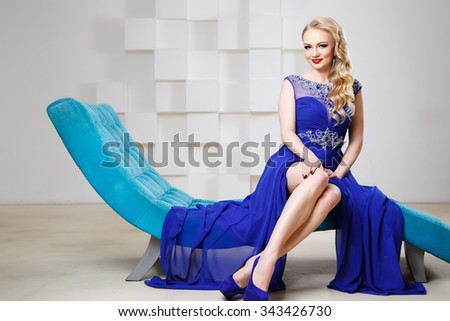 Portrait of gorgeous blonde woman in luxury blue dress with perfect make up and hair style - stock photo