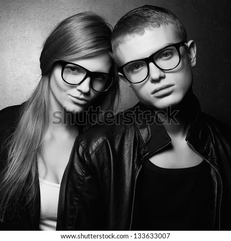 Portrait of gorgeous fashion twins in black clothes wearing trendy glasses and posing over gray background together. Perfect hair. Natural make-up. Perfect skin. Hipster style. Monochrome studio shot.