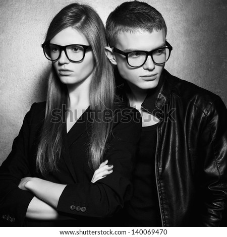 Portrait of gorgeous fashion twins in black clothes wearing trendy glasses and posing over metal background together. Perfect hair and skin. Natural make-up. Hipster style. Black and white studio shot - stock photo