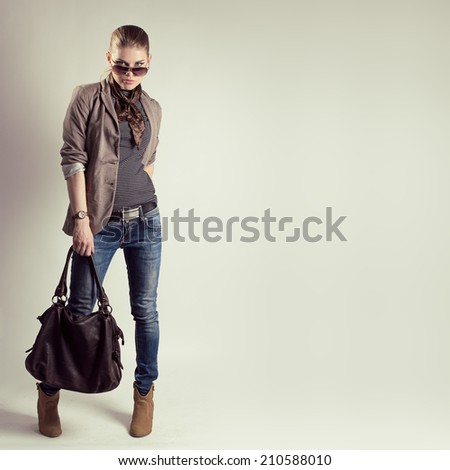 Portrait of gorgeous fashion woman in sunglasses holding stylish leather bag. Young beautiful Caucasian female model wearing fashionable jeans, jacket and high heels shoes.  - stock photo