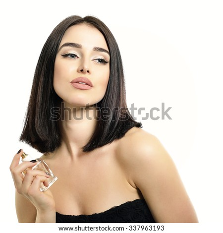 Portrait of gorgeous lady with perfume, young beautiful woman holding bottle of perfume and smelling aroma over white background