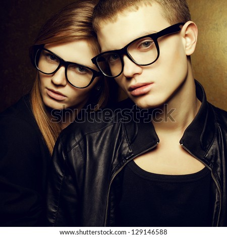 Portrait of gorgeous red-haired fashion twins in black clothes wearing trendy glasses and posing over golden background together. Studio shot. - stock photo