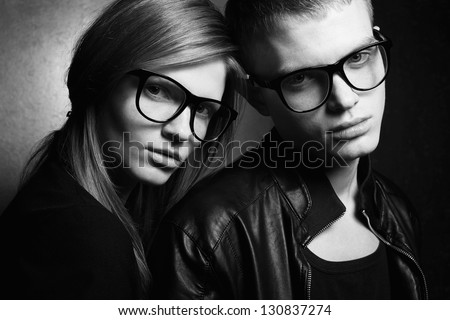 Portrait of gorgeous red-haired fashion twins in black clothes wearing trendy glasses and posing over golden background together. Black and white (monochrome) studio shot. - stock photo