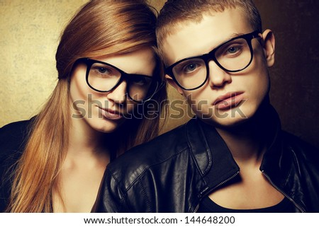 Portrait of gorgeous red-haired fashion twins in black clothes wearing trendy glasses and posing over golden background together. Perfect hair & skin. Hipster style. Close up. Studio shot - stock photo