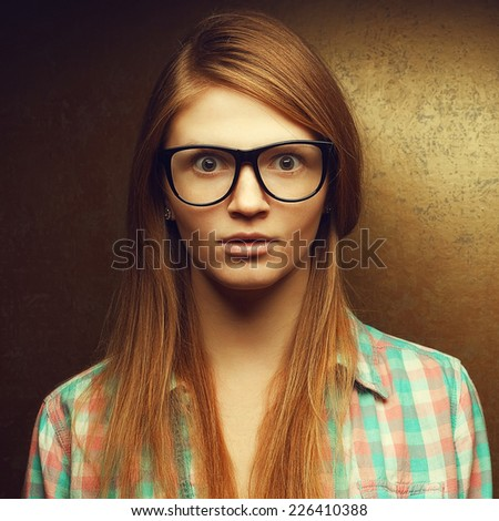 Portrait of gorgeous red-haired (ginger) fashionable girl in casual shirt wearing trendy glasses and posing over golden background with wow (scared) face. Hipster style. Studio shot - stock photo
