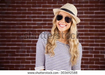 Portrait of gorgeous smiling blonde hipster with sunglasses and straw hat against red brick background - stock photo