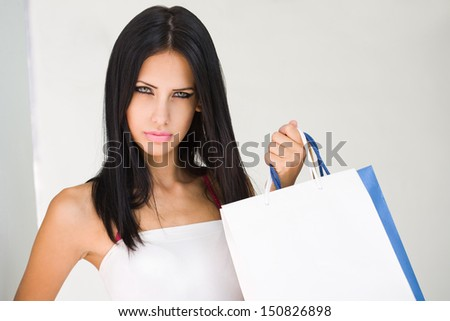Portrait of gorgeous tanned young brunette woman holding shopping bags.
