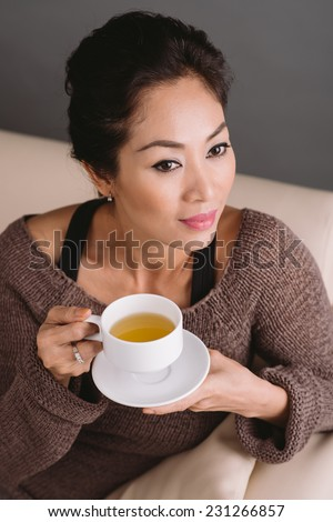 Portrait of gorgeous Vietnamese woman with a cup of green tea