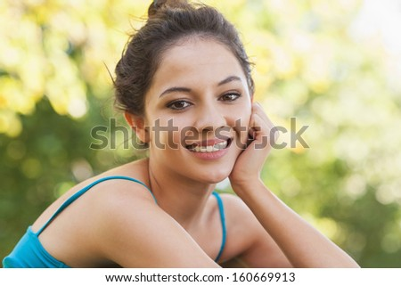 Portrait of gorgeous woman sitting in a park smiling at camera