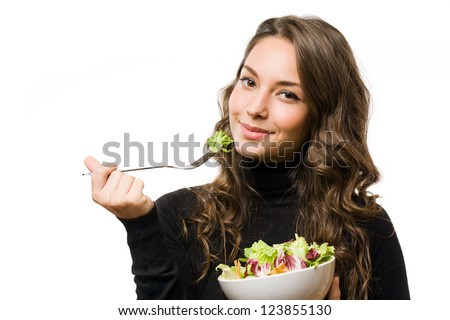 Portrait of gorgeous young brunette eating juicy fresh salad. - stock photo