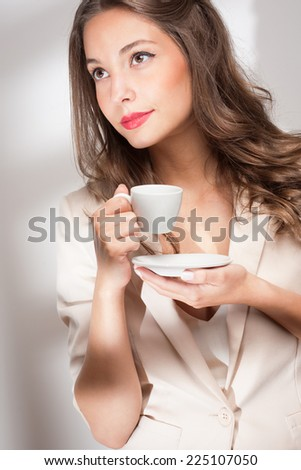 Portrait of gorgeous young brunette woman holding cup of coffee. - stock photo