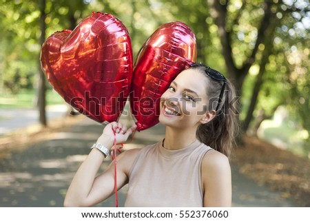 Portrait of gorgeous young brunette woman holding heart shaped balloons.