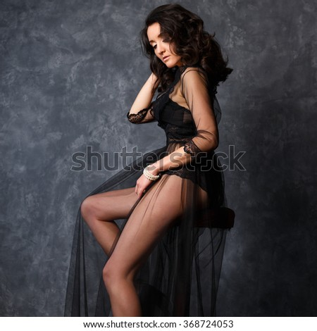 Portrait of gorgeous young brunette woman in a transparent black dress