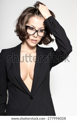 Portrait of gorgeous young caucasian attractive sexy business woman or secretary wearing black jacket and glasses - stock photo