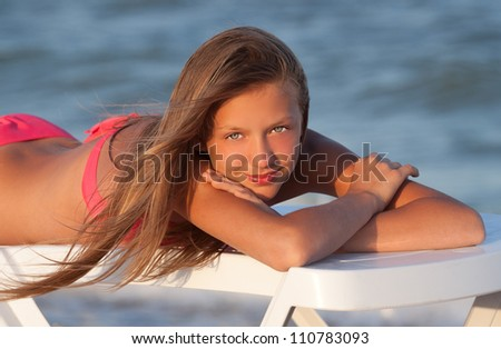Portrait of gorgeous young girl  smiling while looking at you on the beach