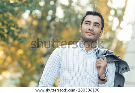 Portrait of gorgeous young hispanic man. Outdoor - outside. Guy in shirt with coat over his shoulder posing in a forest. Autumn beautiful day - stock photo