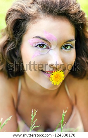 Portrait of Gorgeous young pretty brunette woman relaxing in sunny spring park in white cloth with beautiful curly hair on bright green grass laying with dandelion - stock photo