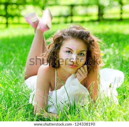 Portrait of Gorgeous young pretty brunette woman relaxing in sunny spring park in white cloth with beautiful curly hair on bright green grass laying - stock photo