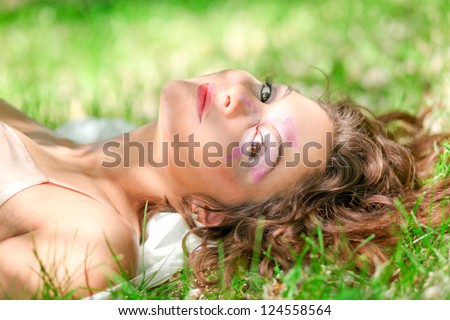 Portrait of Gorgeous young pretty brunette woman with flower relaxing and laying in sunny spring park in white cloth with beautiful curly hair on bright green grass - stock photo