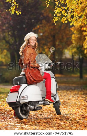 Portrait of gorgeous young woman on scooter posing in the park - stock photo